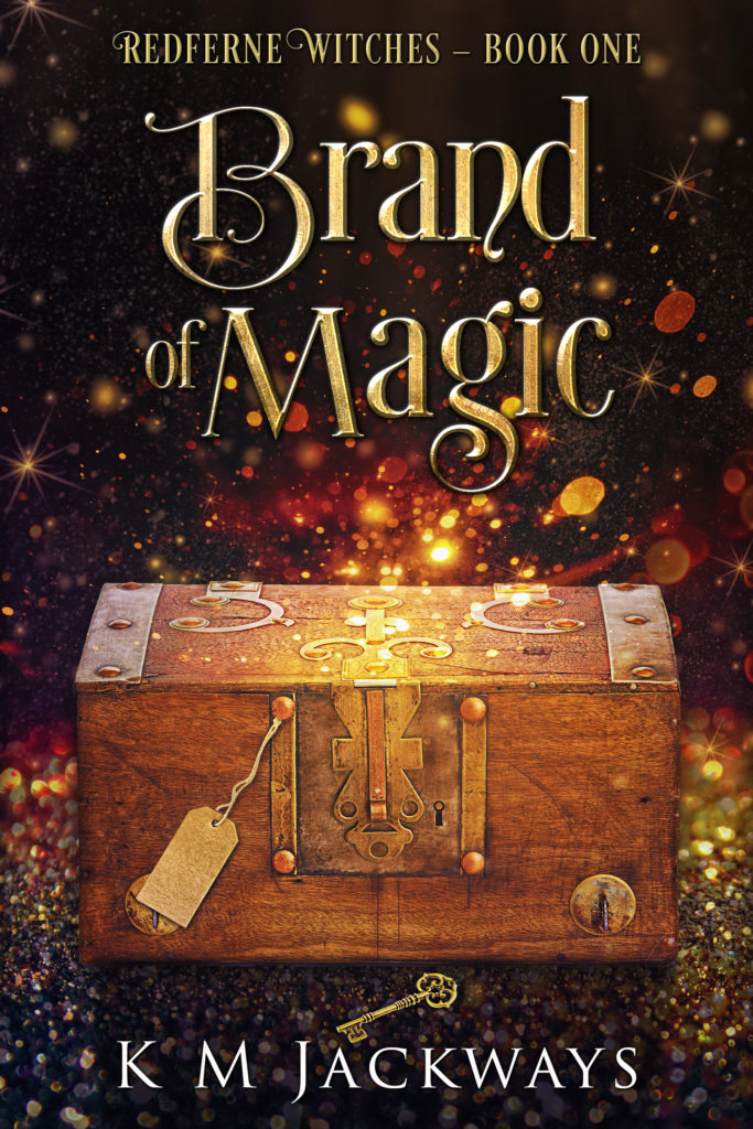 Cover of A Brand of Magic - A wooden chest with ornate symbols, a tag on the front, and a golden key on the floor